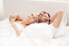 Lyckliga par som hemma ligger i säng Royaltyfria Bilder