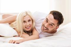 Lyckliga par som hemma ligger i säng Royaltyfri Foto