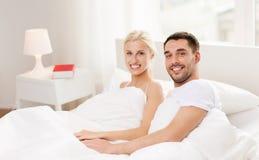 Lyckliga par som hemma ligger i säng Arkivbilder