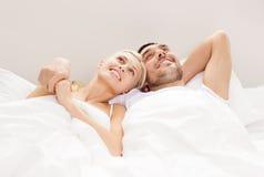 Lyckliga par som hemma ligger i säng Arkivfoto