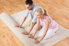Lyckliga par som hemma rullar ut matta eller filten Royaltyfria Foton