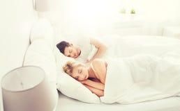 Lyckliga par som hemma sover i säng Royaltyfria Bilder