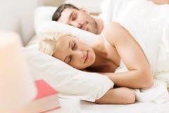 Lyckliga par som hemma sover i säng Royaltyfria Foton