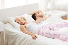 Lyckliga par som hemma sover i säng Royaltyfri Bild