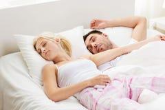Lyckliga par som hemma sover i säng Fotografering för Bildbyråer