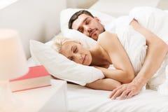 Lyckliga par som hemma sover i säng Royaltyfri Foto