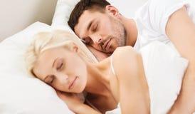 Lyckliga par som hemma sover i säng Royaltyfri Fotografi