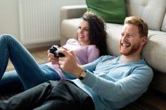 Lyckliga par som hemma spelar videospel Arkivbild