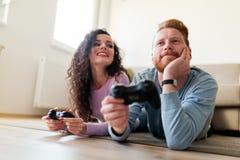 Lyckliga par som hemma spelar videospel Royaltyfria Bilder