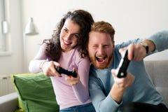 Lyckliga par som hemma spelar videospel Royaltyfri Bild