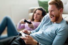 Lyckliga par som hemma spelar videospel Royaltyfria Foton