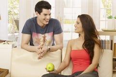 Lyckliga par som hemma talar Royaltyfri Foto