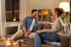 Lyckliga par som hemma talar i afton royaltyfri bild