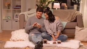 Lyckliga par som hemma tar selfie vid smartphonen lager videofilmer