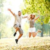 Lyckliga par som jamping i parkera Royaltyfria Foton