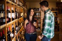 Lyckliga par som köper något vin Arkivbilder