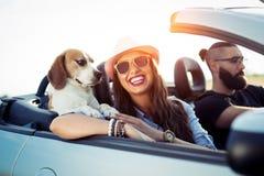Lyckliga par som kör i cabriolet arkivfoto