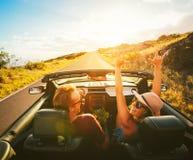 Lyckliga par som kör i cabriolet Fotografering för Bildbyråer