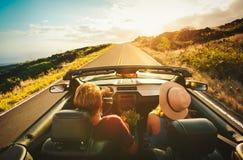 Lyckliga par som kör i cabriolet Arkivbild