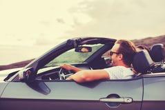 Lyckliga par som kör i cabriolet Arkivbilder