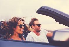Lyckliga par som kör i cabriolet Royaltyfria Bilder