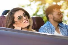 Lyckliga par som kör i konvertibel bil över solnedgång royaltyfri fotografi