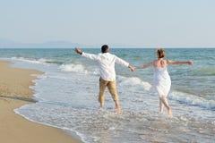 Lyckliga par som kör på stranden Royaltyfri Fotografi