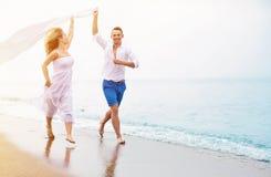Lyckliga par som kör på stranden arkivbild
