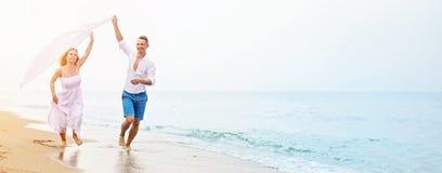 Lyckliga par som kör på stranden arkivfoto