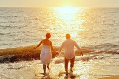 Lyckliga par som kör till havet på stranden arkivfoto