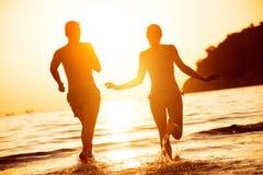 Lyckliga par som körs till solnedgånghavet royaltyfri bild
