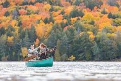 Lyckliga par som kanotar i en sjö i Kanada Arkivbild