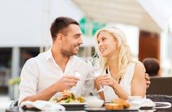 Lyckliga par som klirrar exponeringsglas på restaurangvardagsrummet royaltyfri fotografi