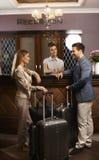 Lyckliga par som in kontrollerar på hotellmottagandet Fotografering för Bildbyråer