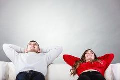 Lyckliga par som kopplar av att vila på soffan hemma Royaltyfri Foto