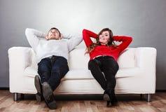 Lyckliga par som kopplar av att vila på soffan hemma Arkivfoto