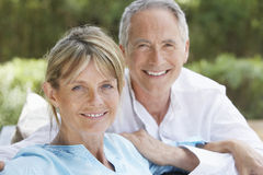 Lyckliga par som kopplar av i trädgård arkivfoto