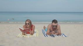 Lyckliga par som kopplar av på stranden arkivfilmer