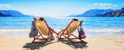 Lyckliga par som kopplar av på stranden royaltyfri bild