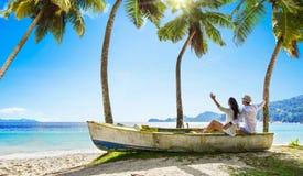 Lyckliga par som kopplar av p? havet Seychellerna ? royaltyfri fotografi