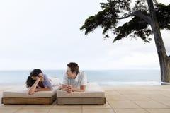 Lyckliga par som kopplar av på Sunbeds vid oändlighetspölen Fotografering för Bildbyråer