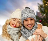 Lyckliga par som kramar över julträd arkivfoton