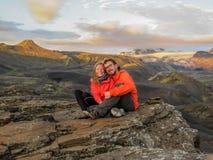 Lyckliga par som kramar att sitta på stenen och att beundra landskapet med höglands- berg, glaciärer och volcanoes på solnedgånge royaltyfri bild