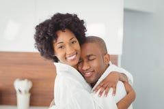 Lyckliga par som kramar i köket royaltyfria foton