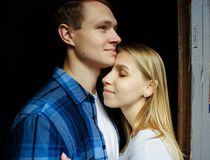Lyckliga par som kramar, närbild som är blond ställning på svart omfamna för bakgrund arkivbild