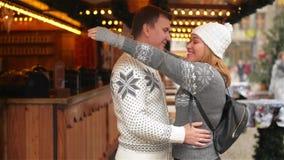 Lyckliga par som kramar på stadsfyrkanten som dekoreras för jul, marknadsför Härlig flicka som kramar grabben på Xmas-mässan lager videofilmer