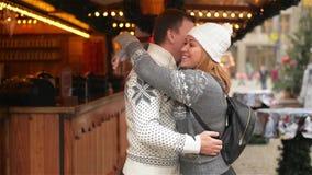 Lyckliga par som kramar på stadsfyrkanten som dekoreras för jul, marknadsför Härlig flicka som kramar grabben på Xmas-mässan stock video