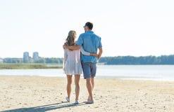 Lyckliga par som kramar p? sommarstranden arkivbild