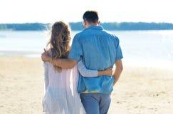 Lyckliga par som kramar p? sommarstranden royaltyfria bilder