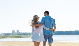 Lyckliga par som kramar p? sommarstranden royaltyfri fotografi